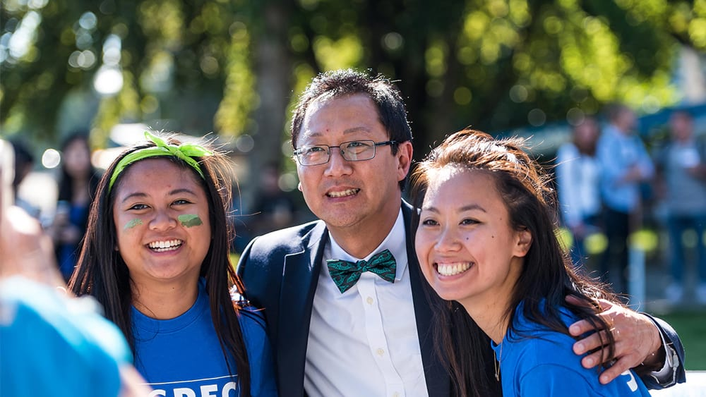 UBC President Santa Ono poses with two students for a photo on Imagine Day. | Photo credit Paul Joseph / UBC Communications & Marketing